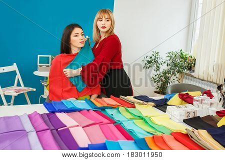 stylist doing color analysis of appearance for girl. Color type test. Image maker determines the colors that best suit an individual based on client natural colorings. Stylist holding colorful shawls