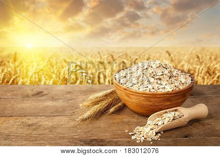 still life ears of oats and uncooked oatmeal in bowl on table with ripe cereal field on the background. Healthy eating for diet and vegan. Golden field on sunset. Photo with place for text