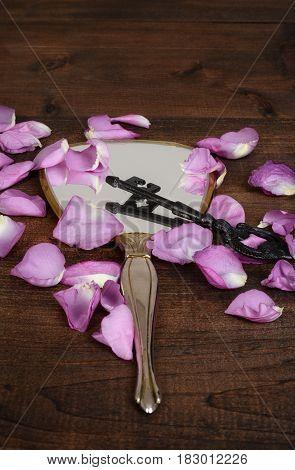 closeup mirror with pink rose petals and a key