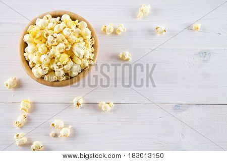 Salty Popcorn In A Wooden Cup Is On A White Table. Popcorn Lies Around The Bowl. Top View.