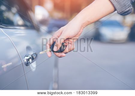 Men's hand using key unlock doors car