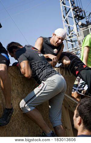 Men are helping each other to jump over a tall fence in a physical challenge competition Legion Run held in Sofia Bulgaria July 2014