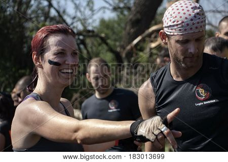 A Woman Is Pointing Ahead Right Beside A Man In A Physical Competition