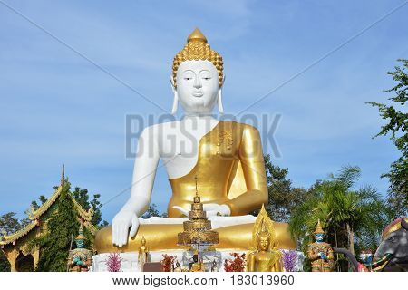 holy big white Buddha image in Wat Phrathat Doi Kham ancient temple in Thailand