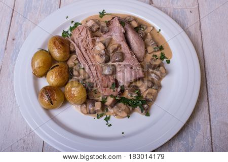 freshly braised turkey's club with mushroom sauce and roasted potatoes
