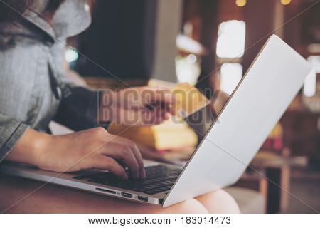 A business woman holding credit card while using laptop in coffee shop