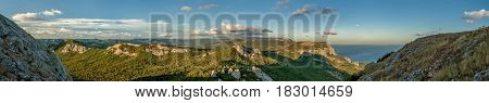 Amazing wide panoramic mountain view of huge natural stone construction with the nice blue sky and little light clouds and the sea in the warm sun light if afternoon in Crimea, Ukraine