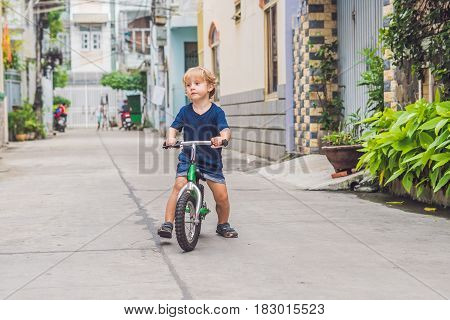Active Blond Kid Boy Driving Bicycle N The Street Of The City. Toddler Child Dreaming And Having Fun