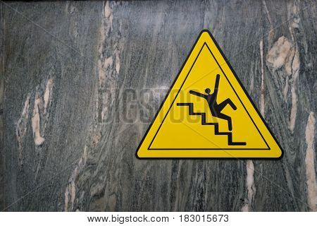 Sign of danger of falling stairs slip warning caution on marble wall.
