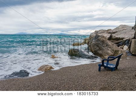 View of the sinking chair in front of the sea with soft gentle waves with foam in the evening
