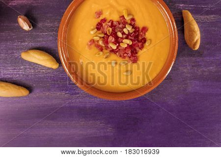 A photo of salmorejo, traditional Spanish cold soup, with bread sticks and crumbs, shot from above on a deep purple wooden texture