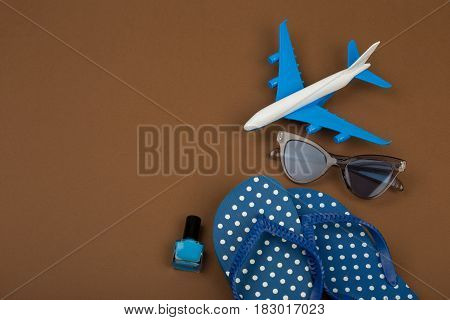 Adventure Time - Plane, Flip Flops, Sunglasses, Nail Polish On Brown Background