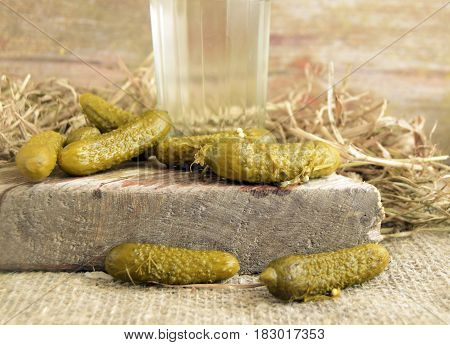 Cucumbers pickles are on a wooden table. Vodka is poured in a glass. Traditional national Russian drink and snack.