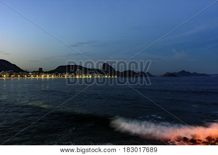 Copacabana Beach and Sugar Loaf seen at night with its buildings lights sea hills and contours