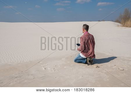 Concentrated Man With A Remote Controller In His Hands In A Desert