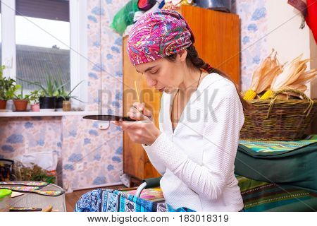 Concentrated Woman Is Fascinated By Painting On Wood