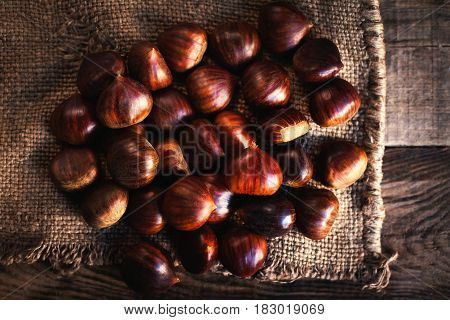 Fresh chestnuts on brown sack bag. Big ripe tasty Chest nuts on old wooden table with copy space close up