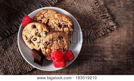 Chocolate chip cookies on white plate dark old wooden table with red raspberry and place for text. freshly baked. Selective Focus with Copy space.