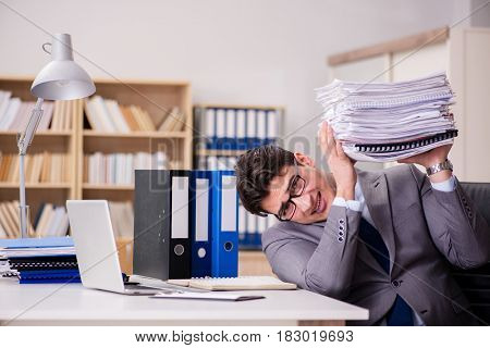 Businessman struggling with stacks of papers