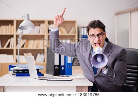 Businessman with loudspeaker in the office