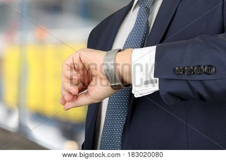 businessman checking time on his watch at the airport