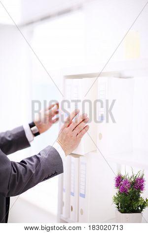 File folders, standing on shelves in background