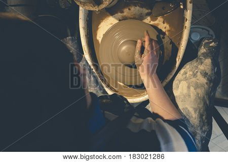 Top view of female potter at work, potter wheel and clay, copy space, toned