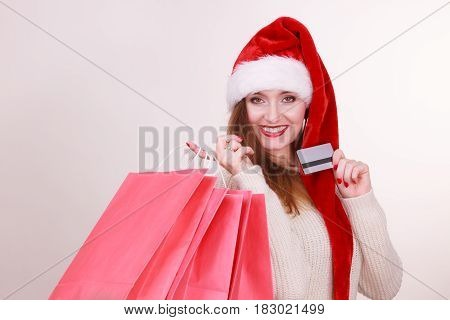 Christmas time. Young latin woman wearing santa claus hat holding red shopping bags and credit card buying gifts