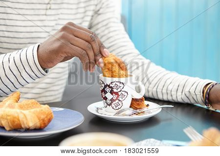 Cropped Image Of Unrecognizable Afro American Man Dunking Croissant Into Cup Of Cappuccino, Enjoying