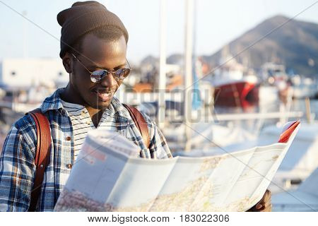 Side View Of Dark-skinned Tourist With Backpack In Trendy Hat And Sunglasses Examining Directions Us