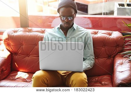 Serious Young Afro American Man On Business Trip Sitting On Red Leather Sofa In Hotel Lobby With Gen