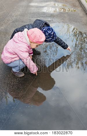 Two small children in warm clothes sit near a puddle and point at it with index fingers