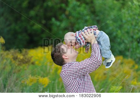 Happy young father holding up in his arms little baby putting him up. Outdoor portrait. Happiness and harmony in family life. Family fun outside. Concept of happy family relations and carefree leisure time
