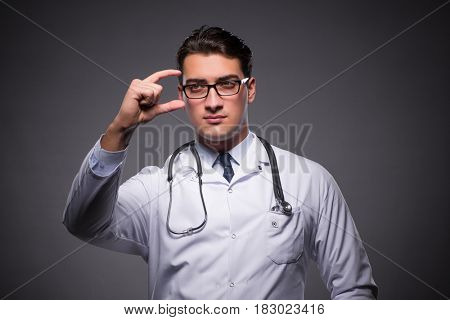 Young doctor against dark background