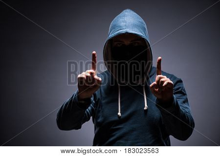 Man wearing hood in dark room