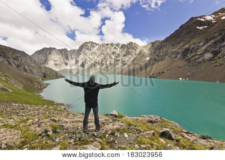 man in black jacket standing with hands up above blue calm mountain lake Alakol with mountains surrounded