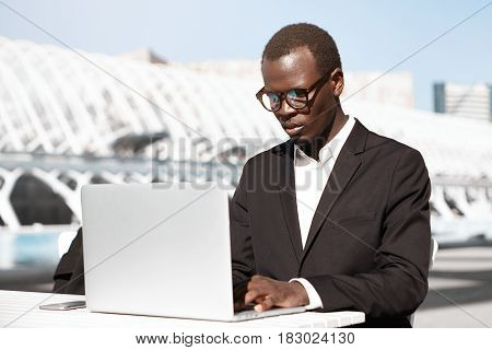 Serious Young Dark-skinned Entrepreneur Wearing Glasses Using Generic Laptop For Remote Work While W