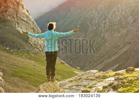 girl in blue jacket standing with hands up above mountain slopes at yellow sunset