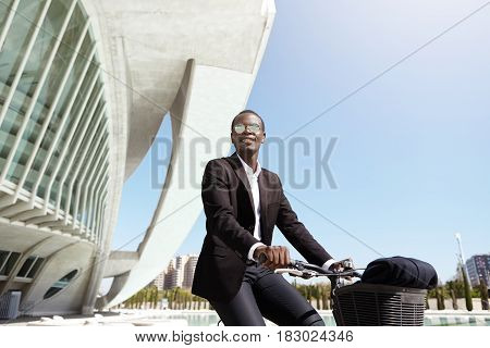 Happy Good-looking African Entrepreneur Riding Bike In Urban Setting On His Way To Office. Successfu