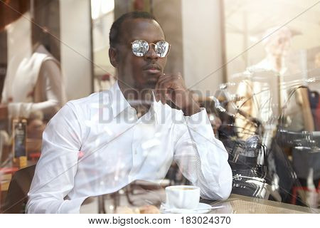 View From Window Glass Of Handsome Pensive Afro American Ceo In White Shirt And Stylish Shades Havin