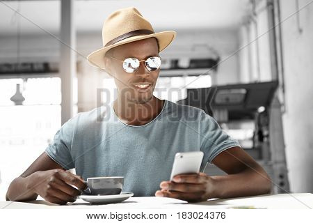 Candid Shot Of Handsome African Student Relaxing At Cafe During Coffee Break Enjoying High-speed Wir