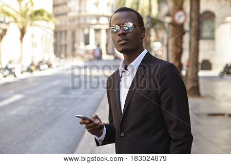 Attractive Successful Young African American Entrepreneur Wearing Black Formal Suit And Mirrored Len