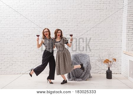 Two happy women, having fun and drinking red wine on party. Fashionable dressed with beautiful wavy hair. On loft white brick wall