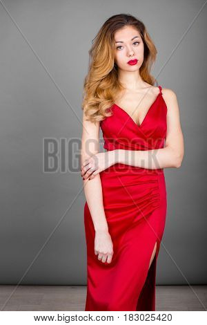 Beautiful young blonde woman in red dress on gray wall studio background