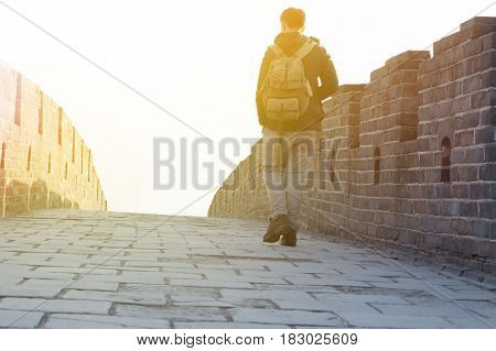 Man walking up and hiking on Great Wall of China during sun set