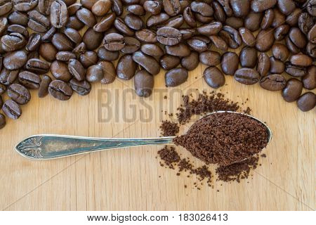 Ground coffee in vintage spoon and coffee beans on wooden table. Shallow depth of field.