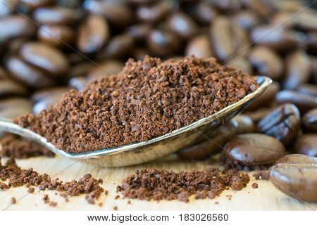 Ground coffee in a spoon and coffee beans on wooden table. Shallow depth of field.