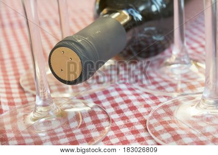 red wine bottle laid between crystal glasses