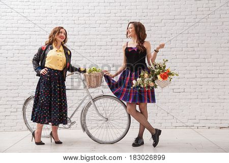 Two young bright beautiful girlfriends with a bicycle and a basket of flowers met and gossip.