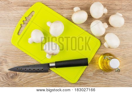 Raw Mushrooms On Yellow Cutting Board, Bottle Of Vegetable Oil